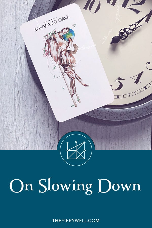 "Pinable Image: Two of Wands Reversed tarot card sitting on an analog wall clock. The words ""On Slowing Down"" in white on teal background."