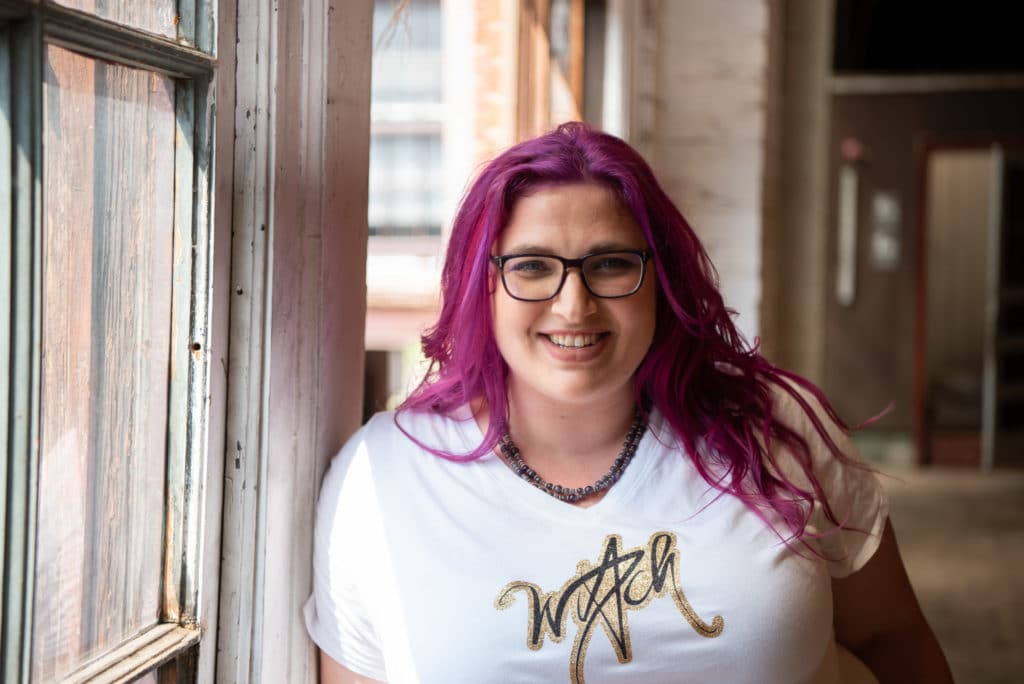 """Patty Ryan Lee leans against a large window frame, smiling, her white shirt says """"witch"""" in glittery handscript."""