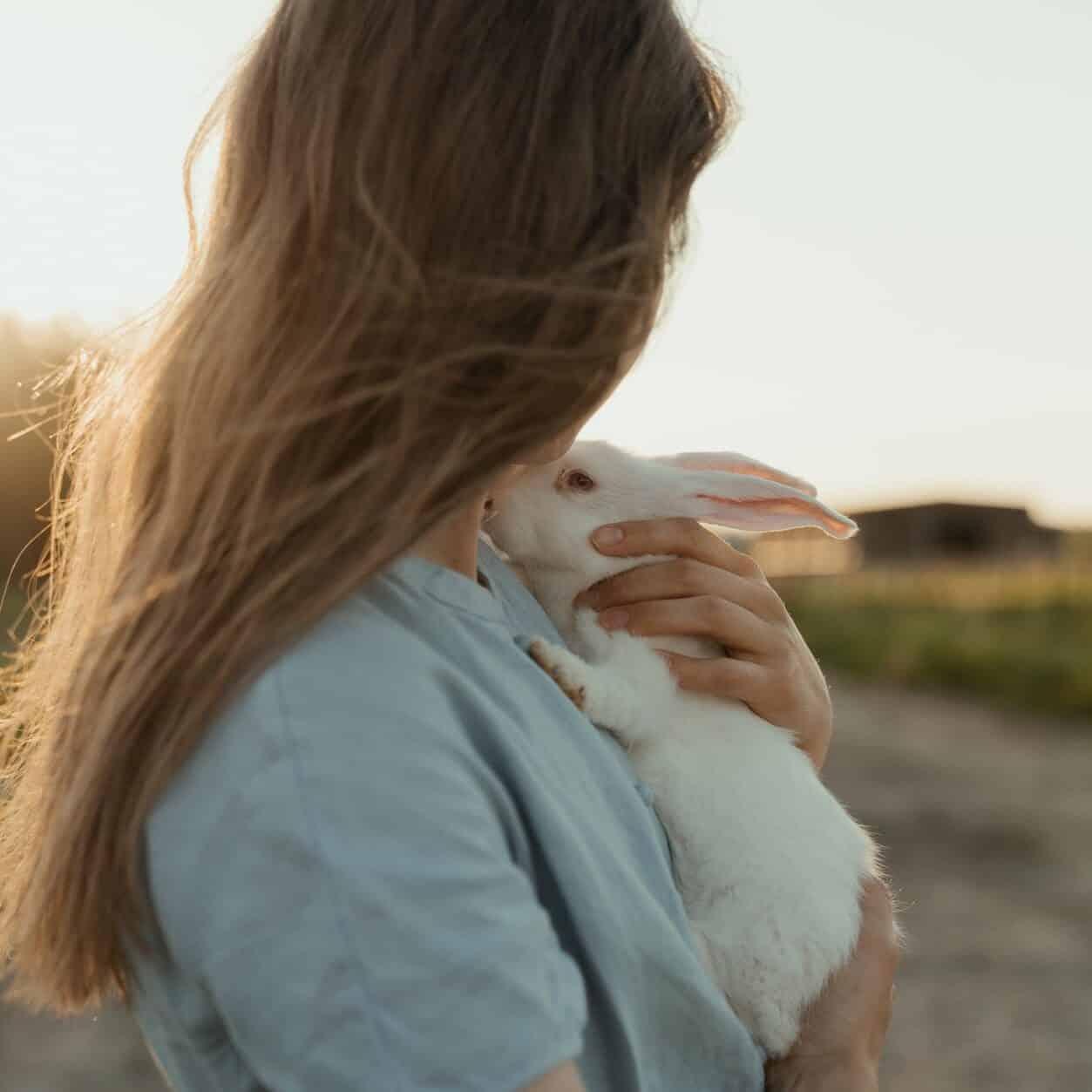 woman in blue long sleeve shirt holding white rabbit plush toy