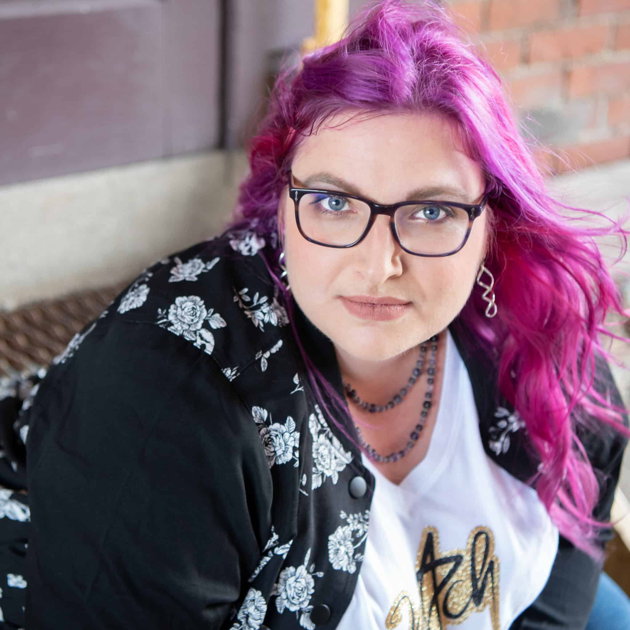 Patty Ryan Lee, with purple hair flowing around her face, gives an intense Mona Lisa smile. Her shirt is white and jacket is black decorated with white roses and skulls.